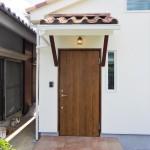 スウェーデン製木製ドアとタイル床のポーチ